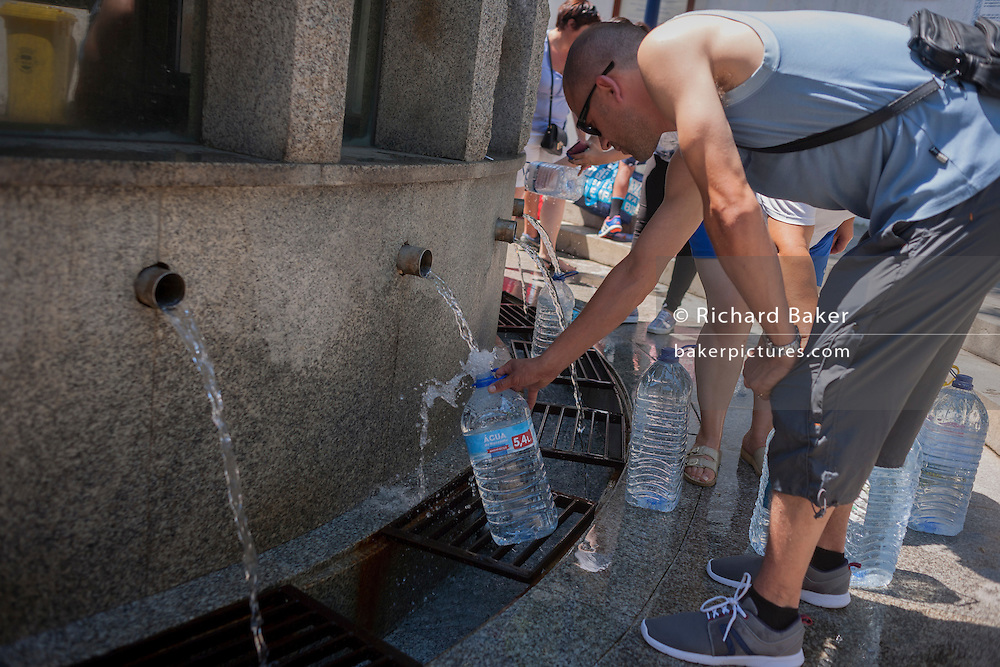 Locals collect thermal spring water using recycled bottles at Fonte de Sao Joao in the spa resort of Luso, Portugal.