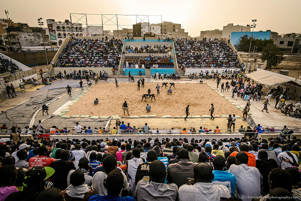 While some wrestlers warm up for their fights at the sidelines of the Iba Mar Diop stadium in Dakar, several duels take place in the center of the arena on March 29, 2015.