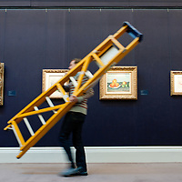 London, UK - 12 April 2013: A Sotheby's employee walks by with a ladder in front of  impressionist paintings including 'Les Pommes' by Paul Cezanne that will go on sale at Sotheby's New York in May 2013. The Blockbuster sales at include works by Richter, Modigliani, Picasso, Rodin, Bacon, Cezanne.