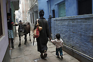 Rahm (middle) leads a child home, Varanasi, India.