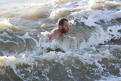 © Licensed to London News Pictures. 20/12/2014. Brighton, UK. A man braves the cold sea water during his daily exercise. Temperatures reaching a maximum of 9C in Brighton and down the South Coast.  Photo credit : Hugo Michiels/LNP
