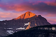 The early light catches the top of  the mountains in a mixture of pinks and magentas from a spectacular sunrise over the Logan Pass region of Glacier National Park, Montana, USA