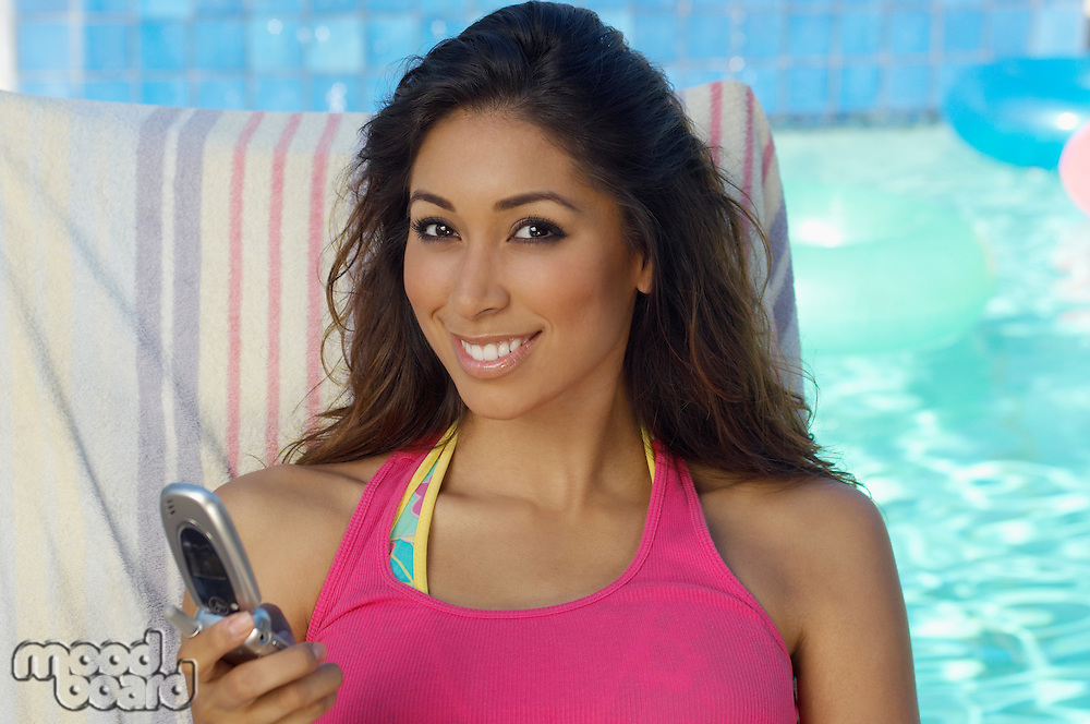 Portrait of woman with mobile phone at swimming pool