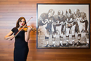 Christina Stanley of Berkeley plays the violin next to a sketch of the Million Dollar Backfield by Samantha Wendell during the Levi's Stadium Art Collection grand opening event at Levi's Stadium in Santa Clara, California, on August 1, 2014. (Stan Olszewski/SOSKIphoto)