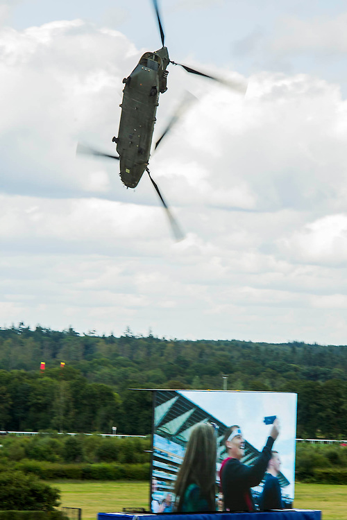 A chinook helicoptre does an acrobatic  display - Red Bull Air Race World Championships at Ascot Race Course. A combination of high speed, low altitude and extreme manoeuvrability make it only accessible to the 'world's most exceptional pilots'. 12 pilots compete in the Master Class category in eight races across the globe for the title of 2014 Red Bull Air Race World Champion. The objective is to navigate an aerial racetrack featuring air-filled pylons in the fastest possible time, incurring as few penalties as possible. All 12 pilots race with a standardised propulsion package – a high-performance, race-tuned standardised engine (Lycoming Thunderbolt) and standardised propellers (Hartzell 3-bladed). They do have a chooice of 3 single engine/seater aircraft - the Zivko Aeronautic Edge 540, the MXS-R and the Hungarian University of Aviation's Corvus Racer 540 - all cappable of around 230kts and of surviving high G forces, 10+. A new feature of the 2014 Red Bull Air Race World Championship is the debut of the new Challenger Cup, giving a new generation of talented pilots from around the world a chance to race. Entertainement is provided by the Red Arrows and the Breitling Wingwalkers, amongst others.  Ascot Racecourse, High St, Ascot, Berkshire, UK.