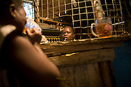 A bar woman servers drinks at the Obama Base bar in the Kibera slum of Nairobi, Kenya June , 2008.Kibera is home to nearly 1million people living in an area roughly the size of New York's Central Park with sprawling market places and  PHOTO BY KEITH BEDFORD