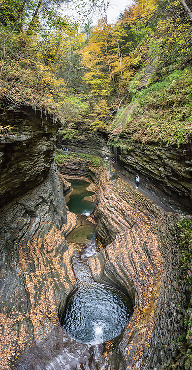 Rainbow Falls. In Watkins Glen, the spellbinding Gorge Trail winds two miles over and under 19 waterfalls of Glen Creek, which descends 400 feet under 200-foot-high cliffs. Watkins Glen State Park is south of Seneca Lake in Schuyler County in the Finger Lakes region New York, USA. The Devonian sedimentary rocks are mostly soft shales, with some layers of harder sandstone and limestone. The vertical panorama was stitched from 12 overlapping photos.