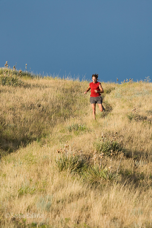 A man in a red shirt trail running in the late afternoon through the Front Range of Colorado