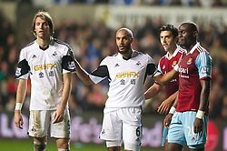 SWANSEA, WALES - Sunday, October 27, 2013: Swansea City's captain Ashley Williams separates West Ham United's Guy Demel and Swansea City's Miguel Perez Cuesta 'Michu' during the Premiership match at the Liberty Stadium. (Pic by David Rawcliffe/Propaganda)