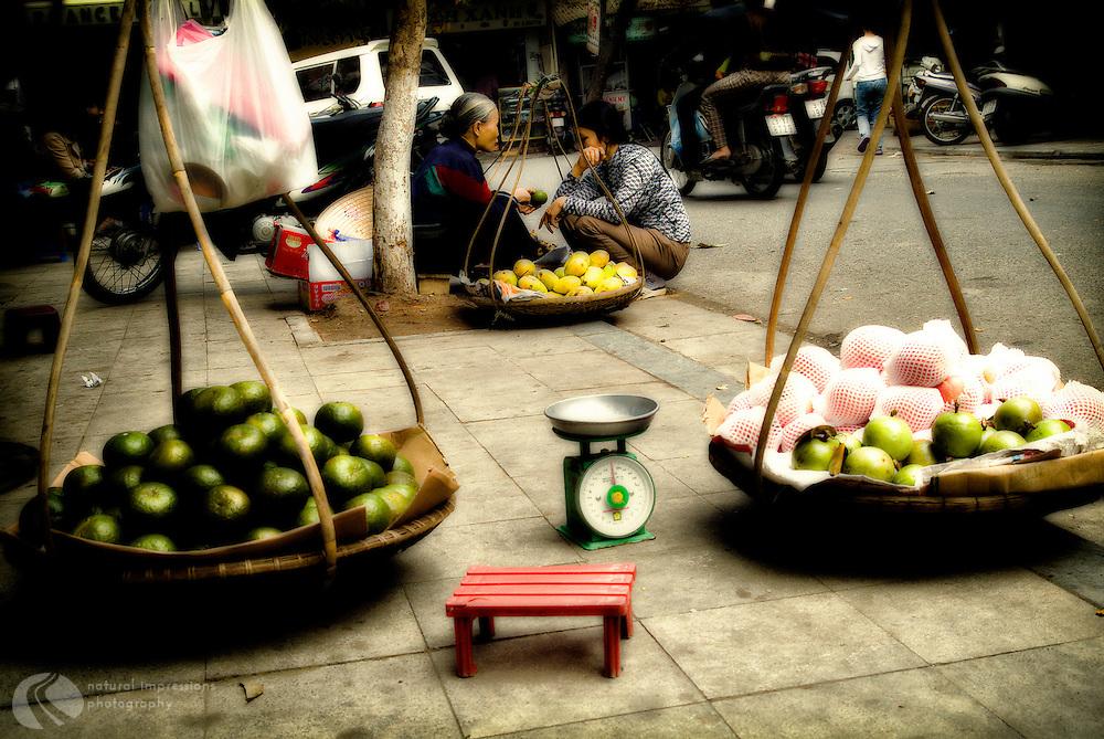 Basket ladies selling fruits in Hanoi.