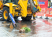 © Licensed to London News Pictures. 06/10/2014. Twickenham, UK. Many plants were floating int he water.  Firefighters help to contain a mains water pipe which has burst in King Street Twickenham today 6th October 2014. It appears that workmen working in the area have used a JCB digger to stem the flow. Many local shops and businesses have been flooded.   Photo credit : Stephen Simpson/LNP