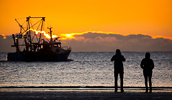 © Licensed to London News Pictures. 02/11/2018. Scarborough UK. People watch a fishing boat leave Scarborough harbour at dawn this morning on a cold but bright start to the day on the Yorkshire coast. Photo credit: Andrew McCaren/LNP