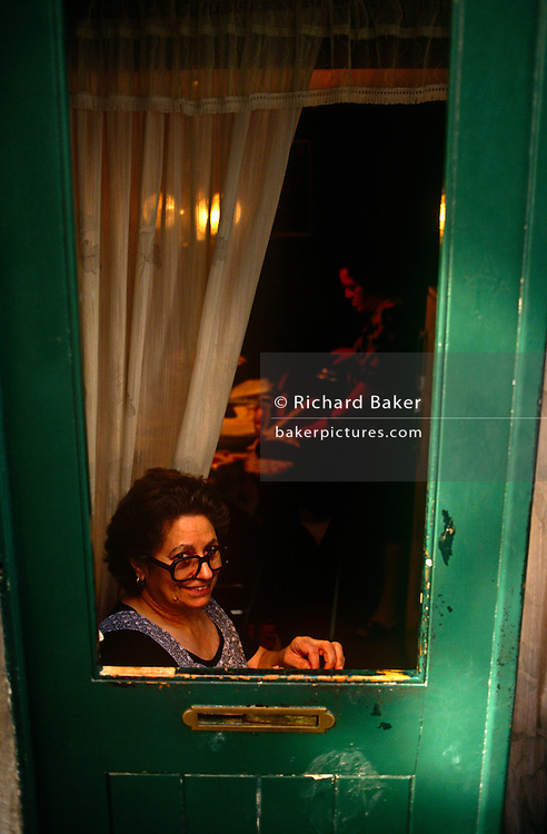 A houswife smiles from her low door in her inner-city home within Lisbon's Bica district of the Portuguese capital.