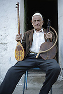 Martin Pisha, 82 years old, inhabitant of Theth, with çifteli and lahuta instruments.  Albania