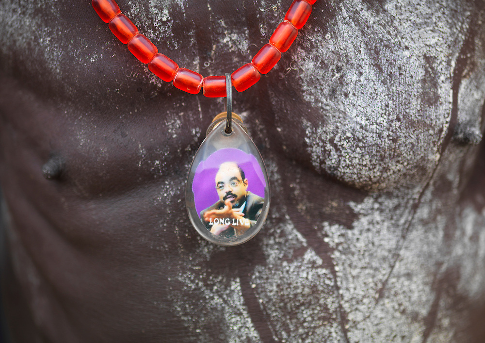 Ethiopia, detail of man with painted chest and pendant depicting portrait of Prime Minister Meles Zenawi.