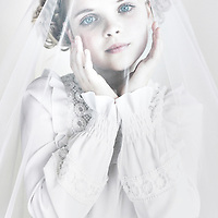 Headshot of young girl with clear blue eyes and blonde hair wearing white lace veil looking at camera