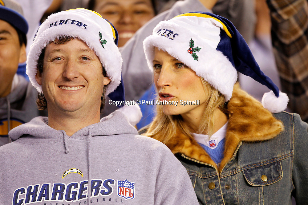 A pair of San Diego Chargers fans wear Christmas hats as they enjoy the NFL week 15 football game against the San Francisco 49ers on Thursday, December 16, 2010 in San Diego, California. The Chargers won the game 34-7. (©Paul Anthony Spinelli)