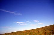 A07WR3 Blue sky wispy clouds and hillside