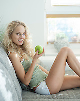 Side view portrait of young woman holding apple while sitting on sofa in house