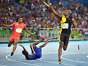 "Usain Bolt of Jamaica celebrates as he crosses the finish line winning gold in the Men's 4 x 100m relay, as America's Justin Gatlin tumbles on the track, during the 2016 Rio Summer Olympics in Rio de Janeiro. Bolt completed the olympic ""Triple-Triple"" with Jamaica's win in the 4x100m. Japan's Asuka Cambridge (L) won silver for his team."