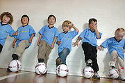 Children line up with the ball, during a class. Here they are learning basic ball control with their feet.