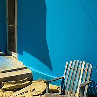 A homemade chair in the sun by a blue wall