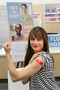 In this photo from the United Nations Foundation, actor Amanda Peet displays her 'bandage of honor' after participating in the Get a Shot, Give a Shot initiative, a partnership between the UN Foundation's Shot@Life campaign and Walgreens, New York, Sept. 26, 2013. From now through October 14, for every vaccine administered at a Walgreens or Duane Read pharmacy, they will donate a life-saving vaccine to children who need them most in developing countries.(INSIDER IMAGES/Stuart Ramson for UN Foundation)