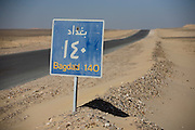 A desert highway road sign for the Egyptian town of Bagdad (not to be confused with Baghdad, Iraq) between Luxor and al-Kharga, Western Desert, Egypt.
