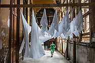 A young boy runs through tablecloths hung to dry in the lower floor of La Guarida, an old house converted into a trendy restaurant. Downtown Havana, Cuba .