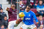 Uche Ikpeazu (#19) of Heart of Midlothian FC and Joe Aribo (#17) of Rangers FC tussle for the ball during the Ladbrokes Scottish Premiership match between Heart of Midlothian and Rangers FC at Tynecastle Park, Edinburgh, Scotland on 20 October 2019.