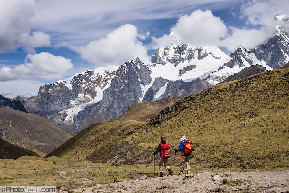 Trekkers walk in Yanayana Valley below Siula Grande. Day 2 of 9 days trekking around the Cordillera Huayhuash in the Andes Mountains, Peru, South America.