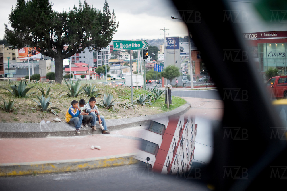 Children sit in a traffic round-about at a busy intersection in Quito, Ecuador.