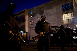 Police patrol outside of a house that was being used as a weapons cache in Ciudad Juarez, Mexico.  Mexico is undergoing a violent war with the nation's drug cartels and Ciudad Juarez has become the murder capital of Mexico, with over 4,000 murders in the past two years.  President Felipe Calderon has dispatched thousands of soldiers and federal police officers in order to contain the situation, but they have not been successful.
