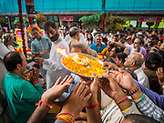 31 AUGUST 2014 - SARIKA, NAKHON NAYOK, THAILAND: People gather around a tray of burning incense and flowers during the Ganesh Festivival at Shri Utthayan Ganesha Temple in Sarika, Nakhon Nayok. Ganesh Chaturthi, also known as Vinayaka Chaturthi, is a Hindu festival dedicated to Lord Ganesh. It is a 10-day festival marking the birthday of Ganesh, who is widely worshiped for his auspicious beginnings. Ganesh is the patron of arts and sciences, the deity of intellect and wisdom -- identified by his elephant head. The holiday is celebrated for 10 days, in 2014, most Hindu temples will submerge their Ganesh shrines and deities on September 7. Wat Utthaya Ganesh in Nakhon Nayok province, is a Buddhist temple that venerates Ganesh, who is popular with Thai Buddhists. The temple draws both Buddhists and Hindus and celebrates the Ganesh holiday a week ahead of most other places.    PHOTO BY JACK KURTZ
