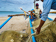 03 AUGUST 2017 - KUTA, BALI, INDONESIA: A man stows his nets on his outrigger canoe on Jimbrana Beach in Kuta. The beach is close to the airport and a short drive from other beaches in southeast Bali. Jimbrana was originally a fishing village with a busy local market. About 25 years ago, developers started building restaurants and hotels along the beach and land prices are rising. The new emphasis on tourism is changing the nature of the area but the fishermen are still busy very early in the morning.     PHOTO BY JACK KURTZ
