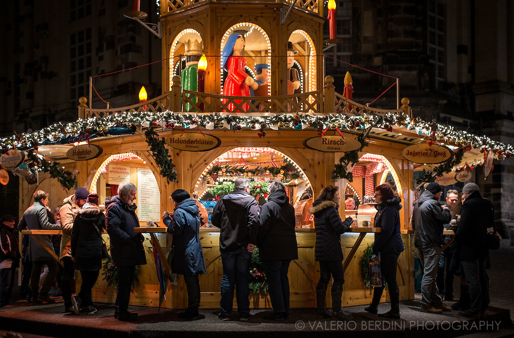 People have a hot alcoholic drink at a stall put up during Christmas in Dresden.