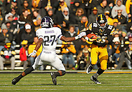 October 26 2013: Iowa Hawkeyes wide receiver Damond Powell (22) tries to avoid Northwestern Wildcats cornerback Matthew Harris (27) after a catch during the third quarter of the NCAA football game between the Northwestern Wildcats and the Iowa Hawkeyes at Kinnick Stadium in Iowa City, Iowa on October 26, 2013. Iowa defeated Northwestern 17-10 in overtime.