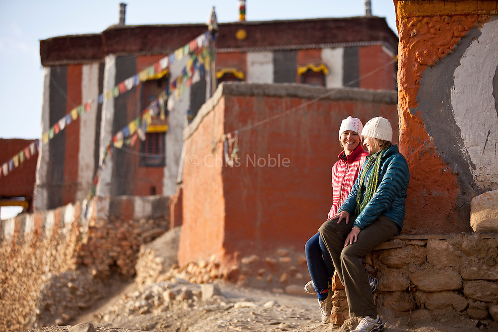 Trekkers Amy Hahn, Jodie Bell & Kinde Nebeker enjoy the sunset seated before the ancient Tsarang monastery (gompa)  in Nepal's Mustang Region.