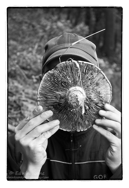 A black and white print of a large mushroom in front of the face of a hiker.