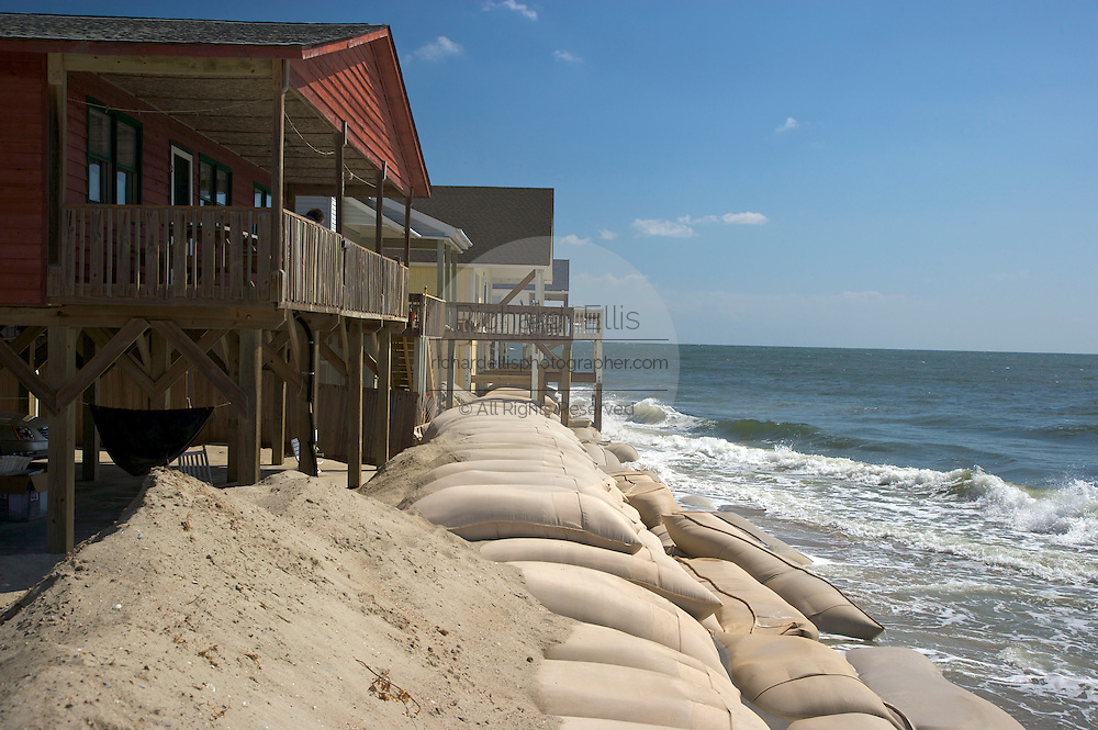 Massive sandbags attempt to hold back the encroaching tide in Ocean Isle Beach, NC where the ocean has reclaimed land, homes and a large section of 2nd Street due to rising tides and erosion. About 3,800 homes are packed together on the narrow seven-mile long Ocean Isle. The rising ocean has worn away at the eastern end, where streets and lots have been steadily disappearing.