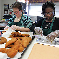 Adam Robison   BUY AT PHOTOS.DJOURNAL.COM<br /> Mooreville High School students Kaylee Ryan, tenth grade, and Charity Betts, twelfth grade, prepare biscuits in Audry Roby's class that will be sold to students at Mooreville High School Tuesday morning.