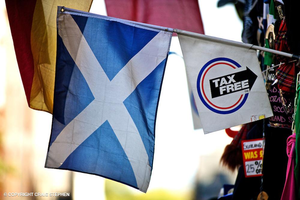 A Scottish saltire hangs next to a tax-free shopping sign on Edinburgh's Royal Mile.