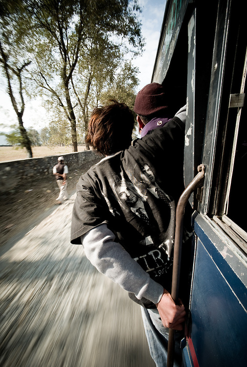 A busboy leans out to call for fares and on the bus to Chitwan.