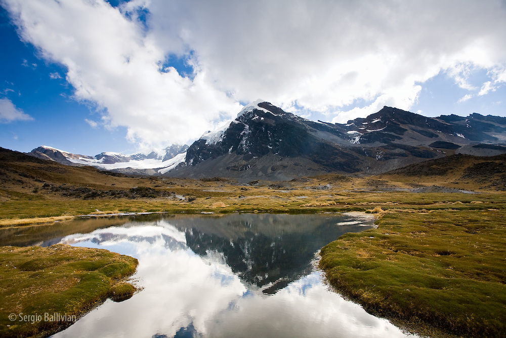 A high-altitude bog lies at the foot of Mt. Cuchillo (18,553'/5,655m) and reflects the surrounding peaks of the Apolobamba Range in Bolivia during winter.