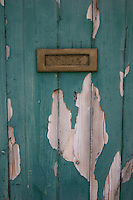 Green door with peeling paint and rusting letterbox