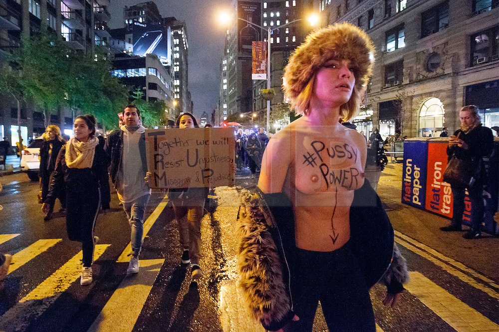 © Licensed to London News Pictures. 09/11/2016. New York, USA. A topless anti-Trump protester marches with thousands of people from Union Square to Trump Tower in New York City, on Wednesday, 9 November 2016 following the presidential election won by Donald Trump. Photo credit: Tolga Akmen/LNP