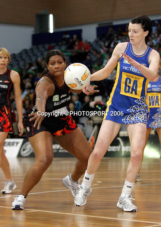 Flames' Vilimaina Davu reaches to take the ball away from Angela Mitchell during the National Bank Cup Round 4 netball match between Otago Rebels and the Canterbury Flames at the Lion Foundation Arena, Dunedin, on Saturday 20 May, 2006. The Canterbury Flames won the match 45-36. Photo: Andrew MacKay/PHOTOSPORT<br /> <br /> 200506 netballer player