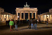 Tourists visit the Brandenburg Gate at night in Berlin Germany. The 18th century Neoclassical monument is built in the Western part of Berlin and is one of the most famous landmarks in Germany. Throughout its existence, the Brandenburg Gate is often a site for major historical events and is considered not only as a symbol of the tumultuous history of Europe and Germany, but also of European unity and peace. (photo by Andrew Aitchison / In pictures via Getty Images)