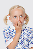 Surprised young girl covering mouth with her hand over white background