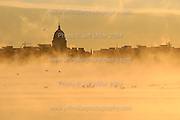 With temperatures near zero degrees during a winter sunrise, a flock of geese swim in the steamy, not-yet-frozen waters of Lake Mendota.  In the background is a silhouette of the Wisconsin State Capitol building and downtown Madison, WI skyline..Photo © Jeff Miller 2004 - all rights reserved.www.jeffmillerphotography.com  ?  608-250-2374.Date:  12/04    File#:   D100 digital camera frame 11206
